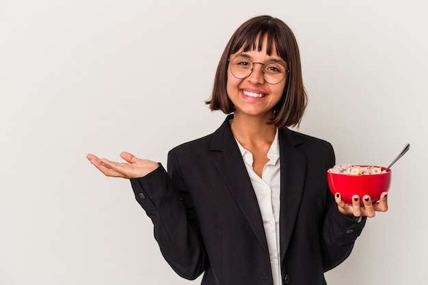 Young mixed race business woman eating cereals isolated on white background showing a copy space on a palm and holding another hand on waist.