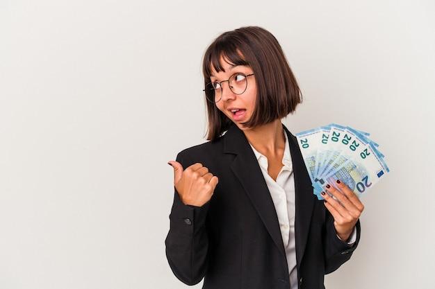 白い背景のポイントに分離された紙幣を親指の指で離れて、笑いながらのんびりと保持している若い混血ビジネス女性。