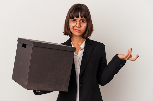 Молодая бизнес-леди смешанной расы, держащая коробку, изолированную на белом фоне, смущена, чувствует себя сомнительной и неуверенной.