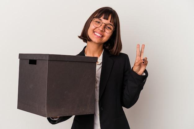 指で平和のシンボルを示す、楽しくてのんきな白い背景で隔離のボックスを保持している若い混血ビジネス女性。
