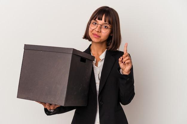 손가락으로 1번을 보여주는 흰색 배경에 격리된 상자를 들고 있는 젊은 혼혈 비즈니스 여성.