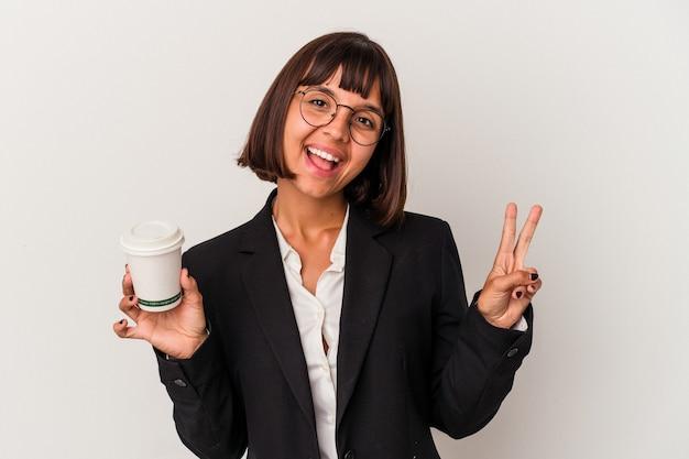 指で平和のシンボルを示す、楽しくてのんきな白い背景で隔離のコーヒーを保持している若い混血ビジネス女性。