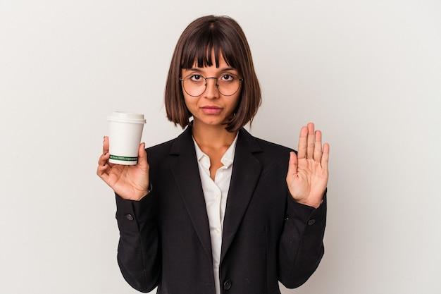 흰색 배경에 격리된 커피를 들고 있는 젊은 혼혈 여성 사업가가 정지 신호를 보여주며 손을 뻗은 채 당신을 방해합니다.