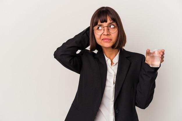 頭の後ろに触れて、考えて、選択をする白い背景で隔離の水のガラスを保持している若い混血ビジネス女性。