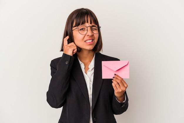 手で耳を覆う白い背景で隔離の手紙を保持している若い混血ビジネス女性。
