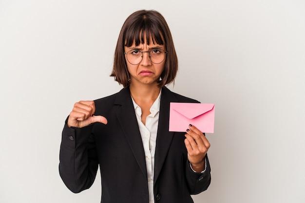 Молодая бизнес-леди смешанной расы, держащая письмо, изолированное на белом фоне, показывает жест неприязни, пальцы вниз. концепция несогласия.