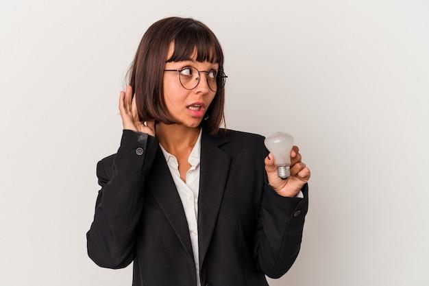 ゴシップを聴こうとしている白い背景で隔離の電球を保持している若い混血ビジネス女性。