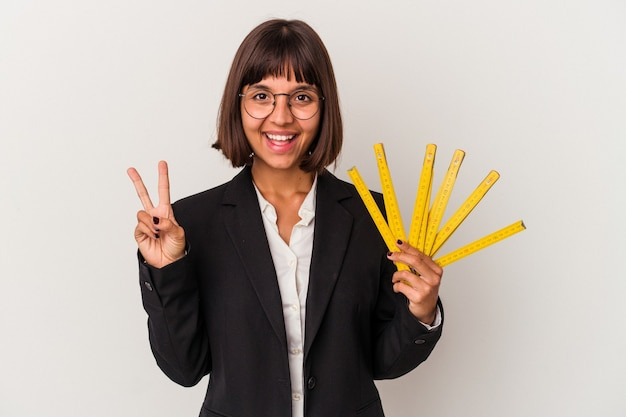 白い背景に分離されたメジャーテープを持っている若い混血ビジネス女性は、指で平和のシンボルを喜んで気楽に示しています。