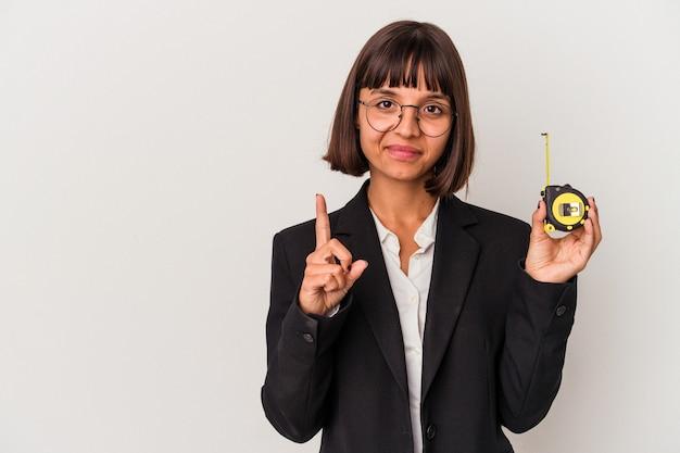 손가락으로 1번을 보여주는 흰색 배경에 격리된 측정 테이프를 들고 있는 젊은 혼혈 비즈니스 여성.