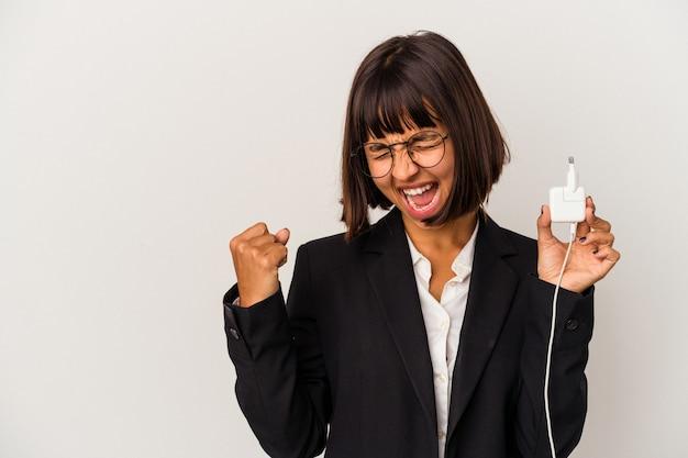 白い背景で隔離の電話充電器を保持している若い混血ビジネス女性は、嬉しい驚きを受け取り、興奮し、手を上げます。