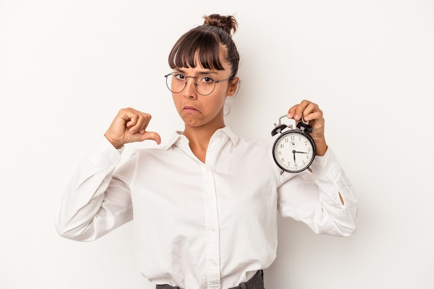 Young mixed race business woman holding an alarm clock isolated on white background  feels proud and self confident, example to follow.