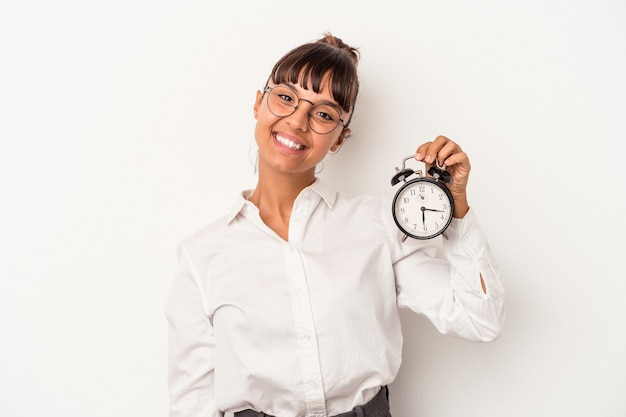 Young mixed race business woman holding an alarm clock isolated on white background  happy, smiling and cheerful.
