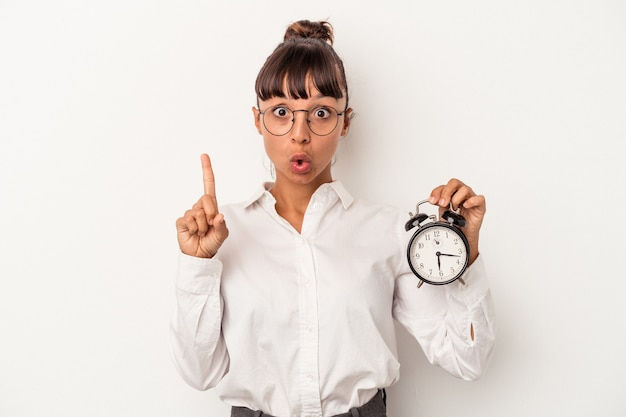 Young mixed race business woman holding an alarm clock isolated on white background  having some great idea, concept of creativity.