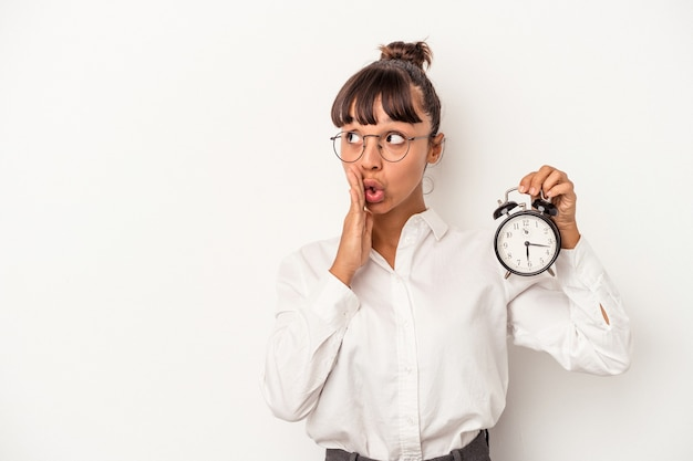 Young mixed race business woman holding an alarm clock isolated on white background  is saying a secret hot braking news and looking aside