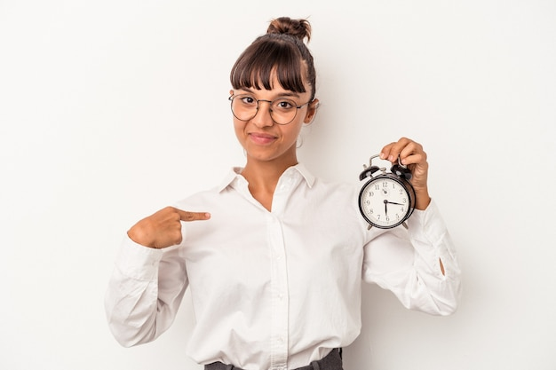 Young mixed race business woman holding an alarm clock isolated on white background  person pointing by hand to a shirt copy space, proud and confident