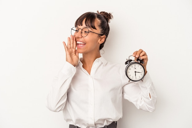 Young mixed race business woman holding an alarm clock isolated on white background  shouting and holding palm near opened mouth.