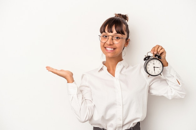 Young mixed race business woman holding an alarm clock isolated on white background  showing a copy space on a palm and holding another hand on waist.