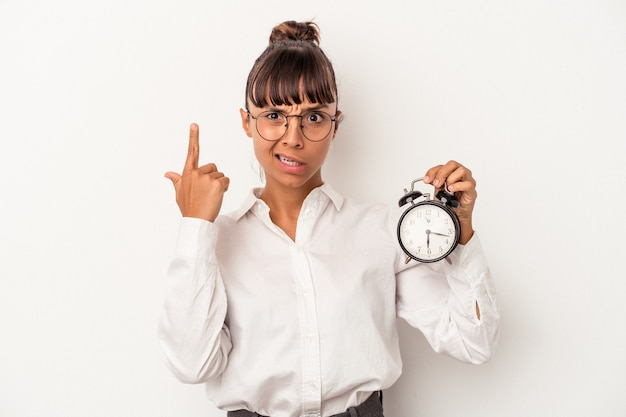 Young mixed race business woman holding an alarm clock isolated on white background  showing a disappointment gesture with forefinger.