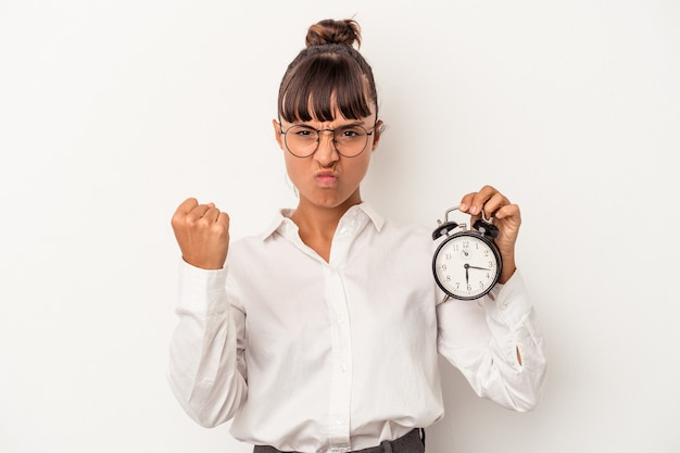 Young mixed race business woman holding an alarm clock isolated on white background  showing fist to camera, aggressive facial expression.