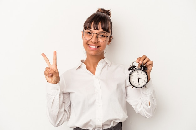 Young mixed race business woman holding an alarm clock isolated on white background  showing number two with fingers.