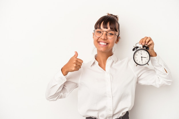 Young mixed race business woman holding an alarm clock isolated on white background  smiling and raising thumb up