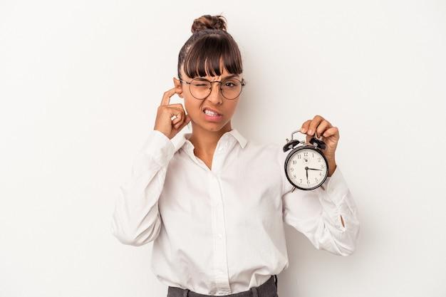 手で耳を覆う白い背景で隔離の目覚まし時計を保持している若い混血ビジネス女性。