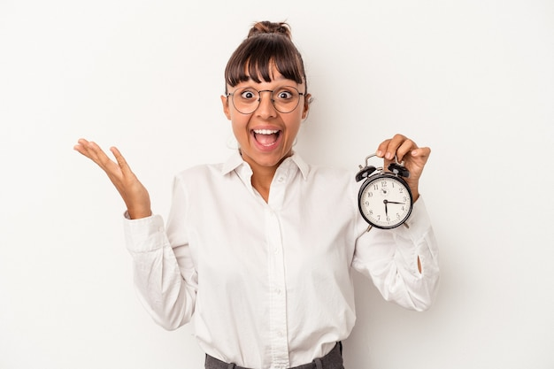 白い背景で隔離の目覚まし時計を保持している若い混血ビジネス女性は、嬉しい驚きを受け取り、興奮し、手を上げます。