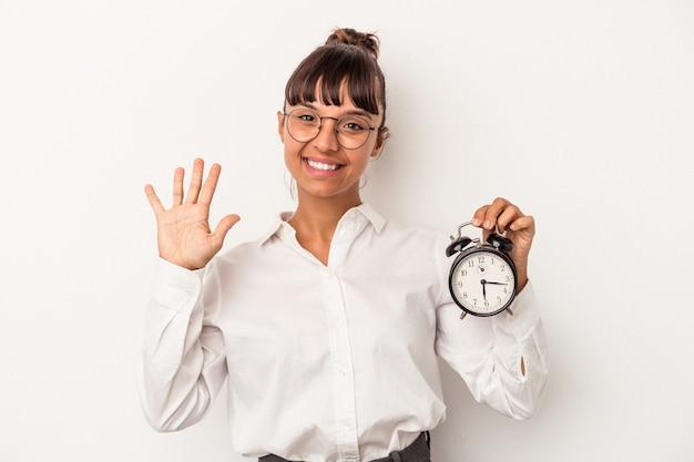 흰색 배경에 격리된 알람 시계를 들고 있는 젊은 혼혈 비즈니스 여성은 손가락으로 5번을 보여주는 명랑하게 웃고 있습니다.