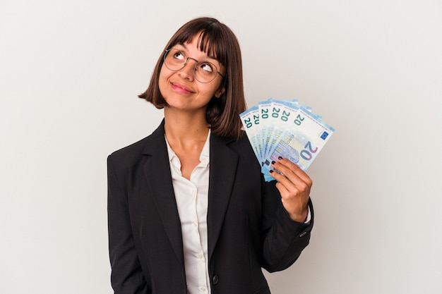 Young mixed race business woman holding a banknotes isolated on white background dreaming of achieving goals and purposes Premium Photo