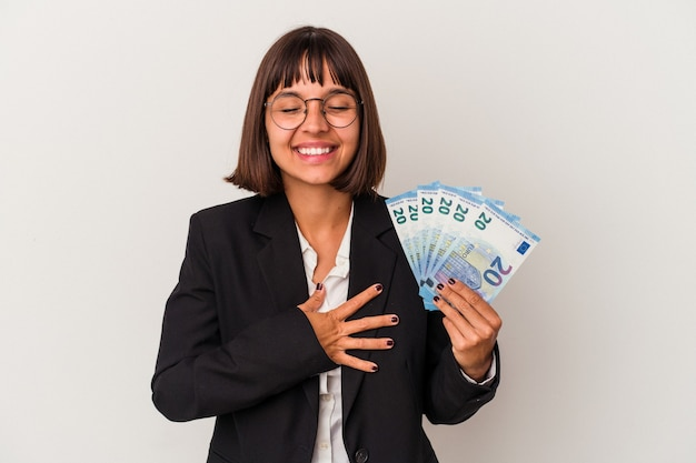 Young mixed race business woman holding a banknotes isolated on white background laughing and having fun.