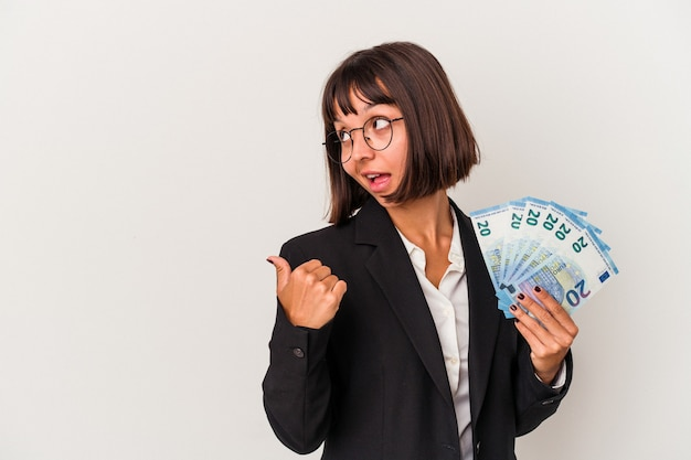 Young mixed race business woman holding a banknotes isolated on white background points with thumb finger away, laughing and carefree.