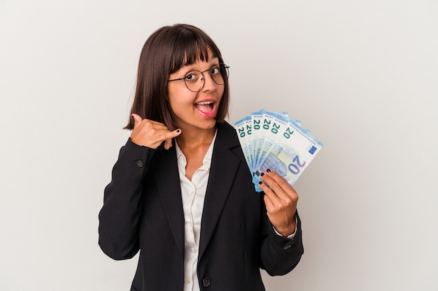 Young mixed race business woman holding a banknotes isolated on white background showing a mobile phone call gesture with fingers.
