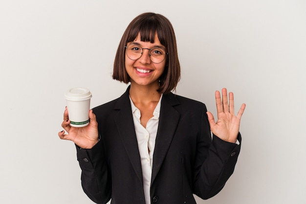 Young mixed race business woman holding a coffee isolated on white background smiling cheerful showing number five with fingers.