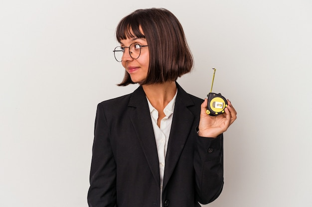 Young mixed race business woman holding a measure tape isolated on white background looks aside smiling, cheerful and pleasant.