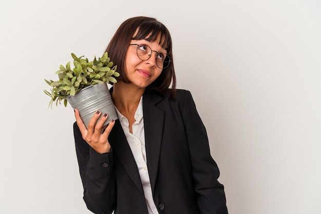 Young mixed race business woman holding a plant isolated on white background dreaming of achieving goals and purposes