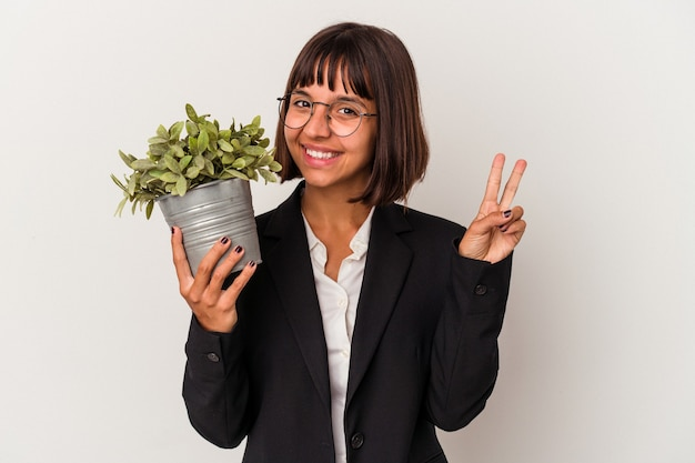 Young mixed race business woman holding a plant isolated on white background showing number two with fingers.