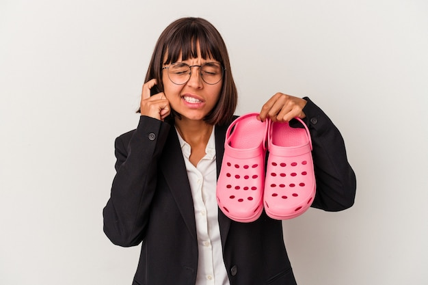 Young mixed race business woman holding sandals isolated on white background covering ears with hands.