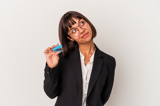 Young mixed race business woman holding a stapler isolated on white background dreaming of achieving goals and purposes