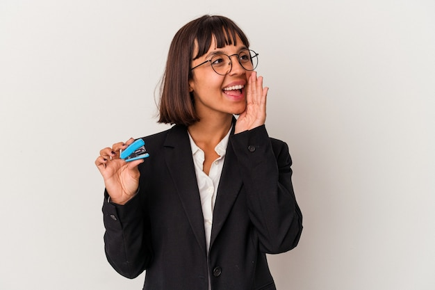 Young mixed race business woman holding a stapler isolated on white background shouting and holding palm near opened mouth.