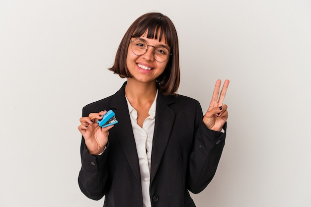 Young mixed race business woman holding a stapler isolated on white background showing number two with fingers.