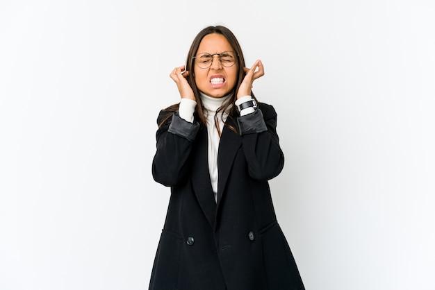 Молодая бизнес-леди смешанной расы изолирована на белом фоне, закрывая уши пальцами, подчеркнутая и отчаянная из-за громко окружающей среды.