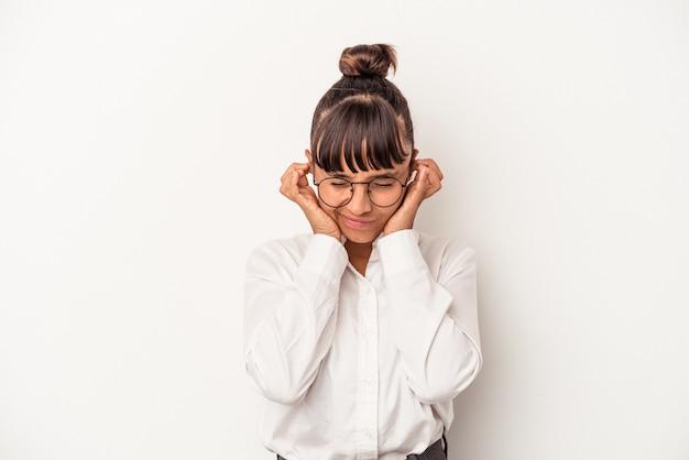手で耳を覆う白い背景で隔離の若い混血ビジネス女性。