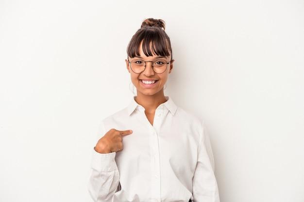 シャツのコピースペースを手で指している白い背景の人に孤立した若い混血ビジネス女性、誇りと自信を持って