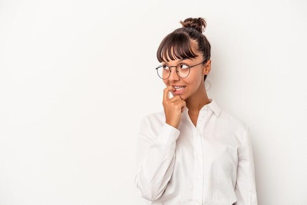 白い背景で隔離の若い混血ビジネス女性は、コピースペースを見ている何かについて考えてリラックスしました。