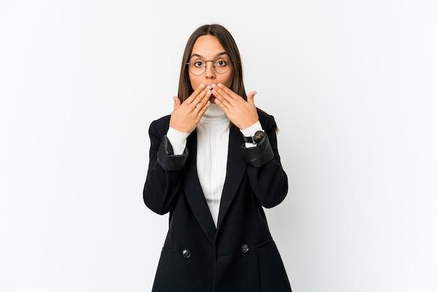 Молодая женщина бизнес смешанной расы, изолированные на белом фоне шокирована, прикрывая рот руками.