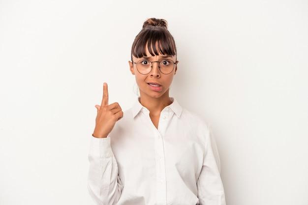 人差し指で失望のジェスチャーを示す白い背景で隔離の若い混血ビジネス女性。