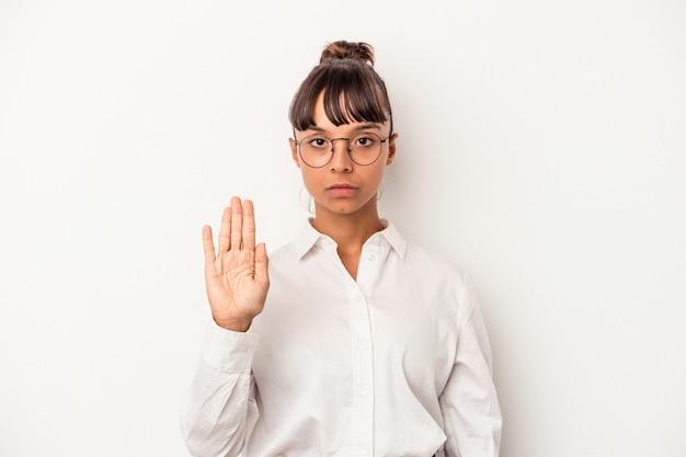 一時停止の標識を示す伸ばした手で立っている白い背景で隔離の若い混血ビジネス女性は、あなたを防ぎます。