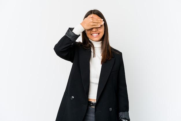 Молодая бизнес-леди смешанной расы, изолированная на белой стене, прикрывает глаза руками, широко улыбается, ожидая сюрприза.