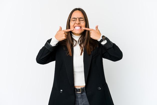 若い混血ビジネスの女性が口に指を指して、白い壁の笑顔に分離されました。