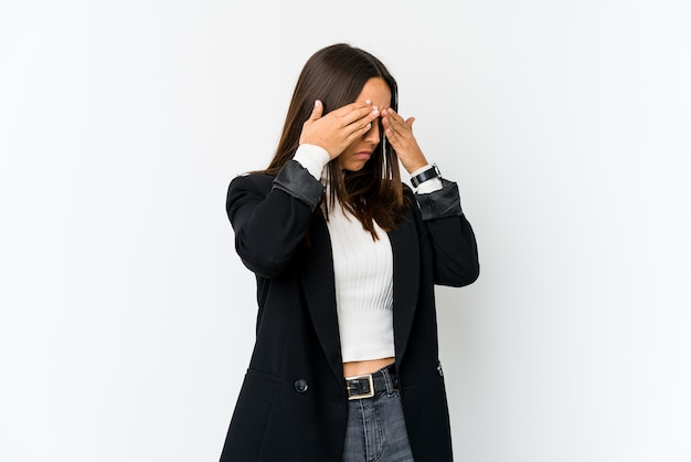 Young mixed race business woman isolated on white background afraid covering eyes with hands.